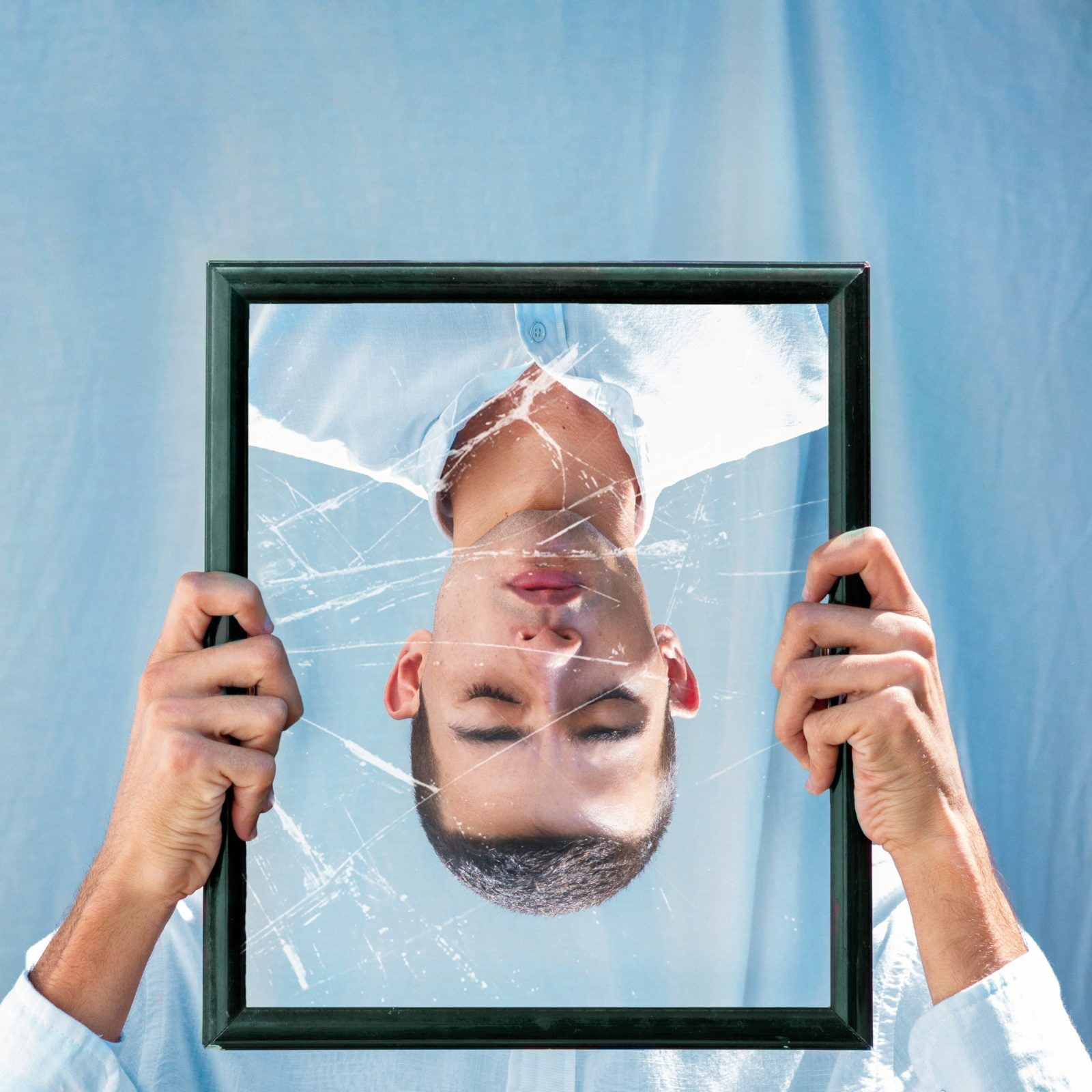 Man holding an upside down broken mirror with his own reflection on it