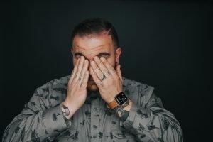 Headache, man covering his eyes
