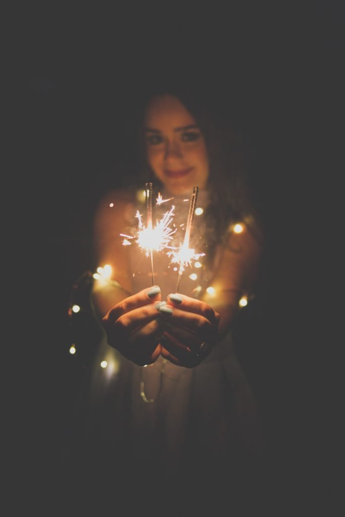 woman carrying two lighted sparklers against black background