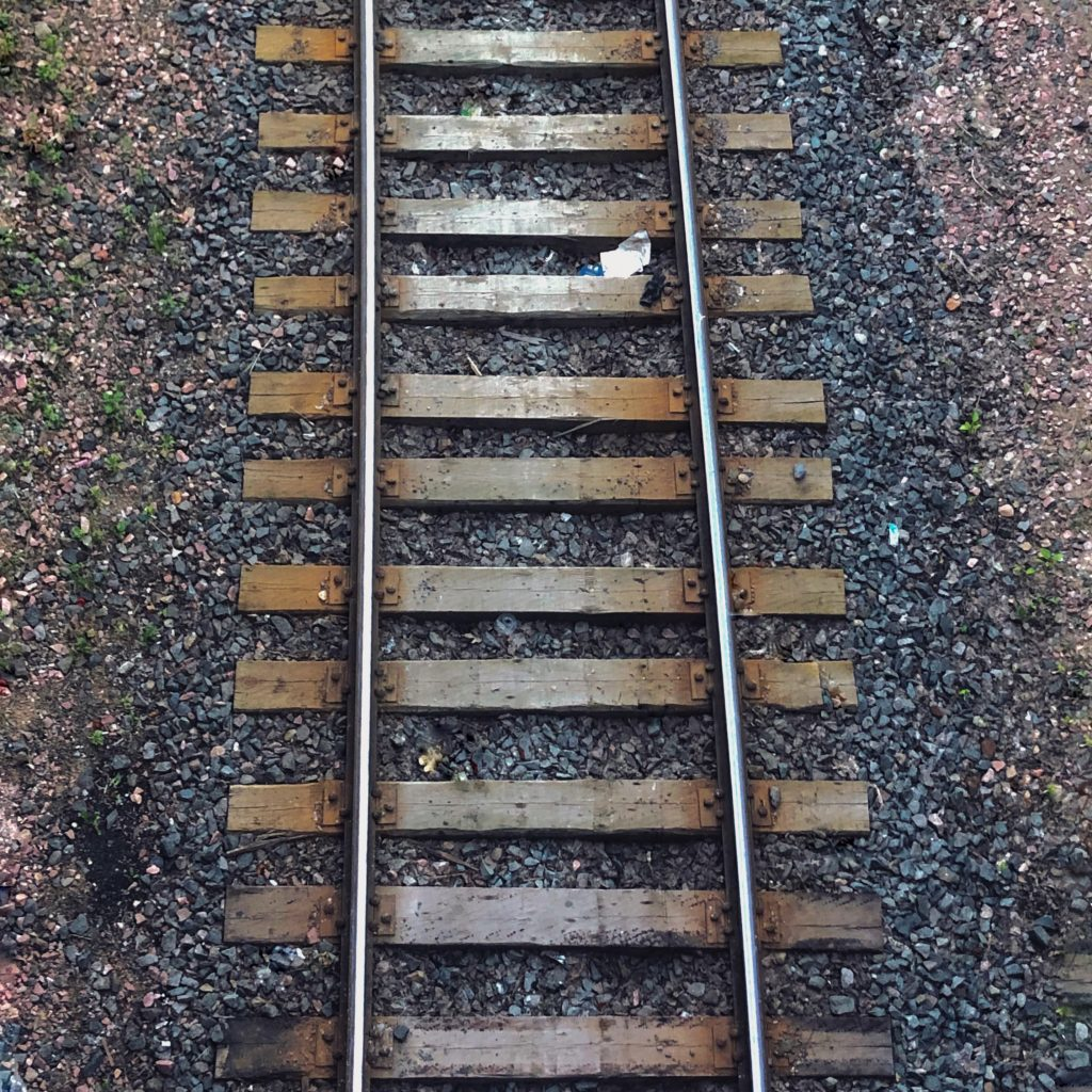 Brown wooden sleepers supporting a rail-track. Lifting them caused qi deficiency in the author when 13.