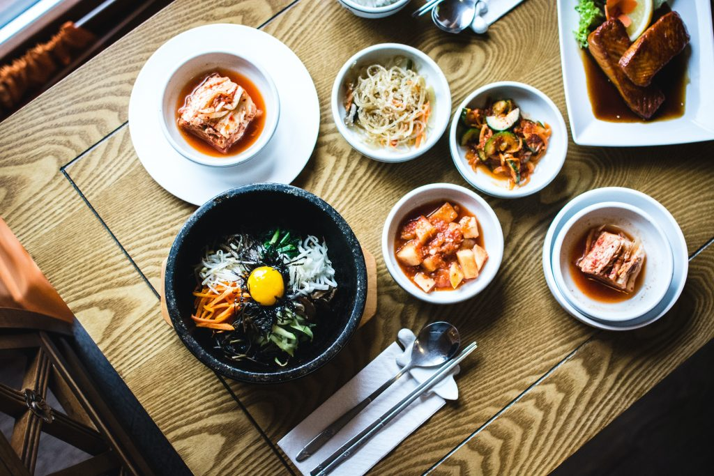 multiple dishes field bowls on table, including fermented kimchi