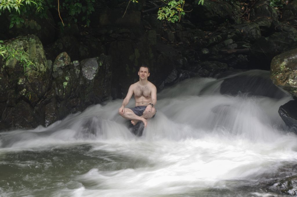 man sitting on rock in waterfall: a form of hydrotherapy
